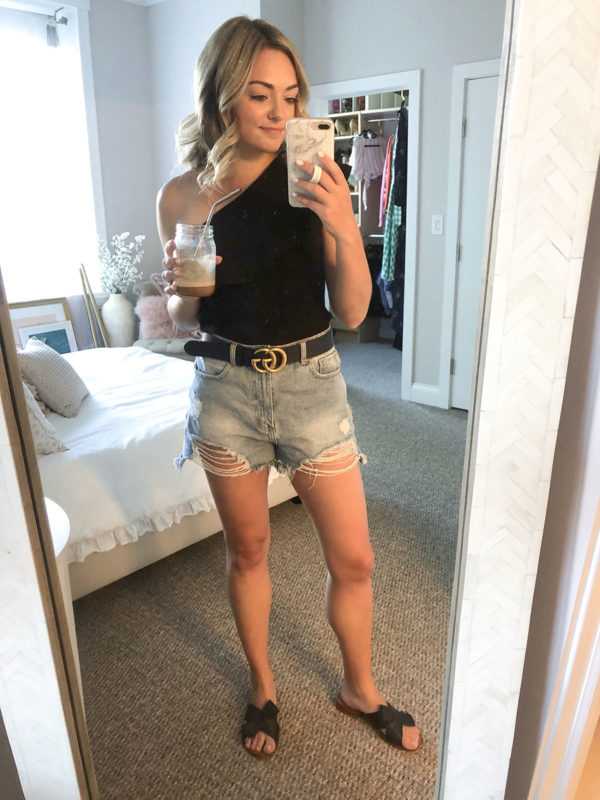 Black one shoulder ruffled top with distressed high waisted jean shorts and a black and gold Gucci belt.