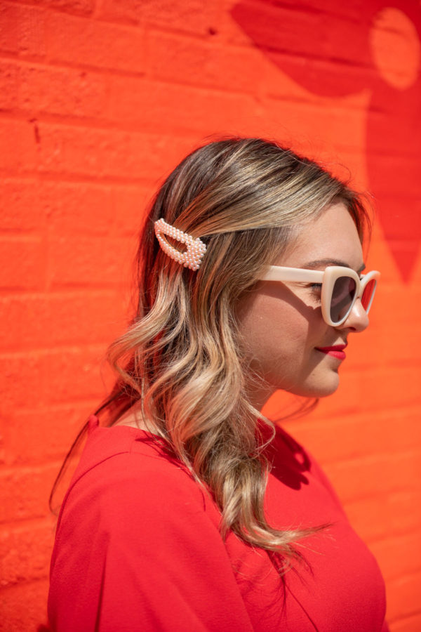 Beauty and lifestyle blogger Bows & Sequins styling a pearl hair clip with white sunglasses.
