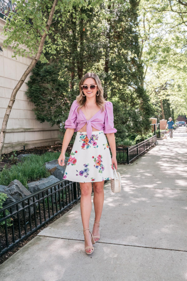 Top Chicago fashion blogger Jessica Rose Sturdy of Bows & Sequins styling an Express Rocky Barnes tie-front crop top with a floral skirt.
