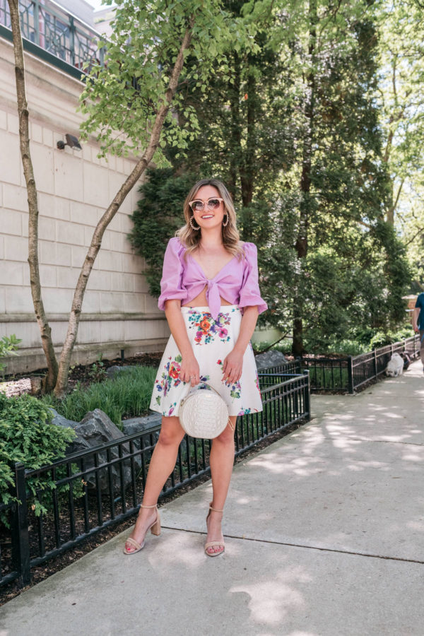 Feminine fashion blogger styling a lavender top with a floral high-waisted skirt.