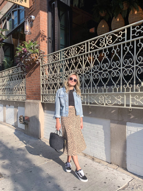 Chicago fashion blogger Jessica Sturdy of Bows & Sequins wearing a leopard print midi skirt with a jean jacket and classic black Vans sneakers.