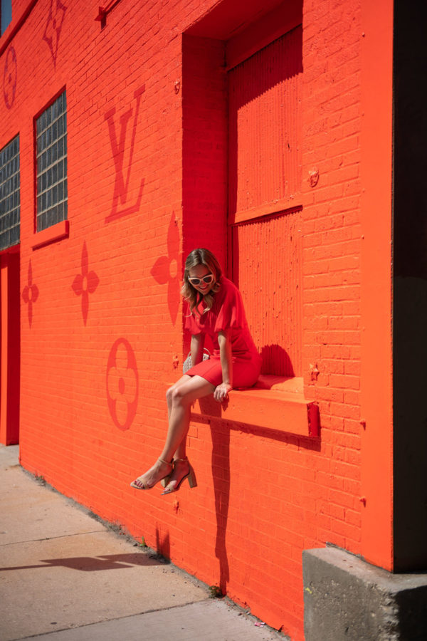 Fashion blogger Bows & Sequins in front of the Louis Vuitton LV orange monogrammed wall on Randolph Row in the West Loop.