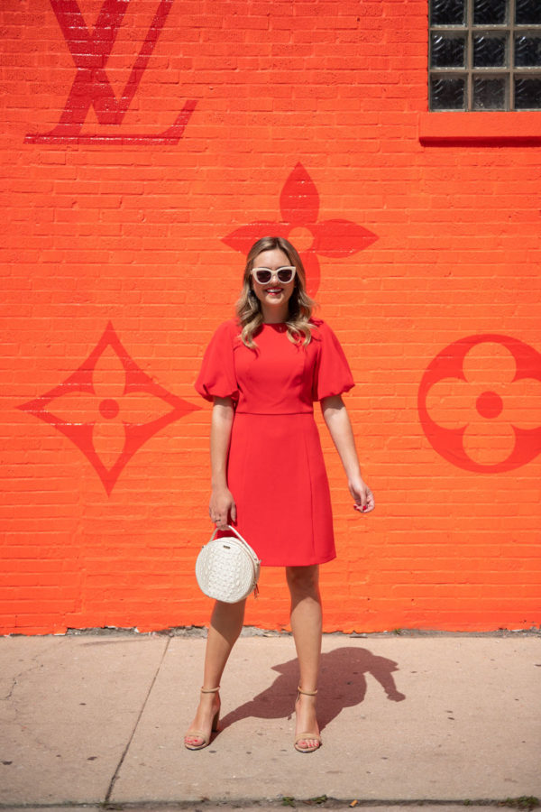 Chicago blogger Jessica Sturdy wearing a red dress in front of the pop-up Louis Vuitton men's store in the West Loop on Randolph.