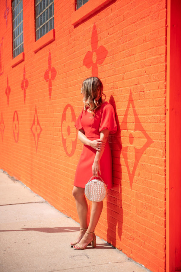 Chicago influencer Bows & Sequins wearing a red dress in front of the Virgil Abloh Chicago pop-up.