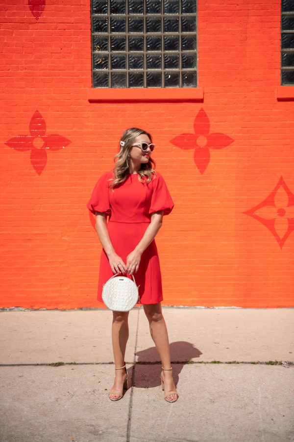 Chicago fashion and beauty influencer Bows & Sequins wearing a pearl hair clip with a red puffy sleeve fit and flare dress.