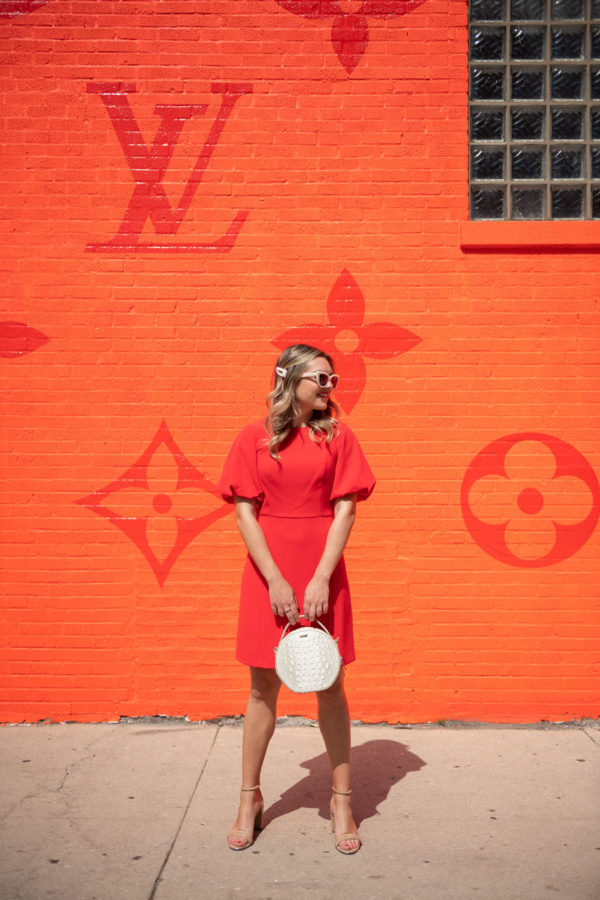 Chicago fashion influencer Bows & Sequins wearing a puff sleeve dress by Eliza J with a white Brahmin handbag.