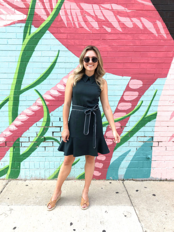 Chicago blogger Jessica Sturdy of Bows & Sequins in front of the pink flamingo wall in River North wearing a preppy green dress with a cute collar and ruffle hem.