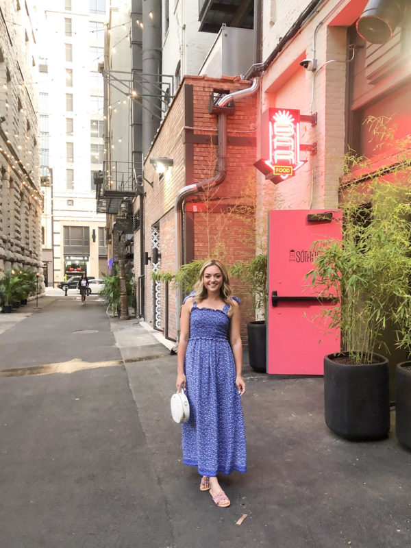 Blue floral smocked maxi dress with tie-shoulder straps and blush pink studded slide sandals outside of Bar Sotano in Chicago