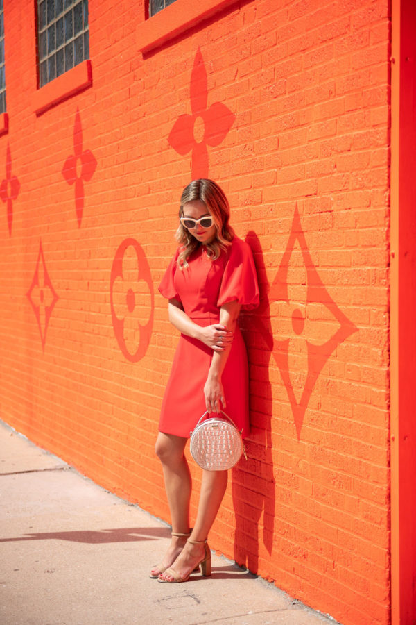Chicago fashion blogger Bows & Sequins styling a red puff sleeve dress in front of the LV monogram wall.