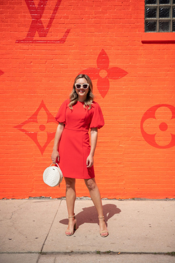 Chicago personal stylist Jessica Sturdy wearing a red puff sleeve dress in front of the West Loop Louis Vuitton pop-up.