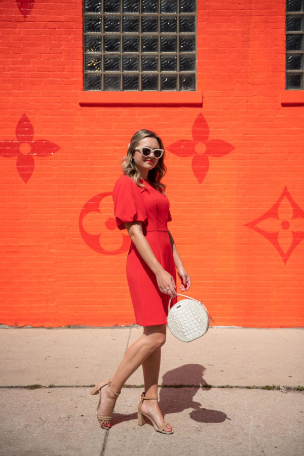 Chicago stylist Jessica Sturdy wearing a red dress in front of the orange Louis Vuitton pop-up.