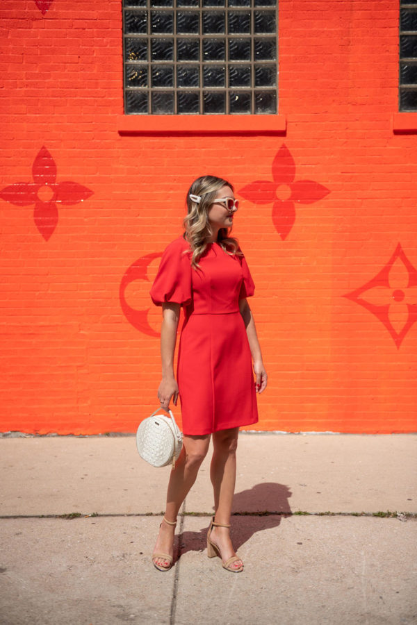 Chicago fashion blogger Bows & Sequins wearing a red dress in front of the Louis Vuitton orange wall.