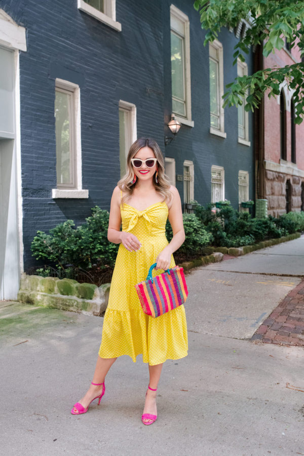 Chicago lifestyle and travel blogger Jessica Sturdy of Bows & Sequins styling a polka dot tiered midi dress with a colorful straw tote, Vince Camuto pink heels, and white sunglasses.