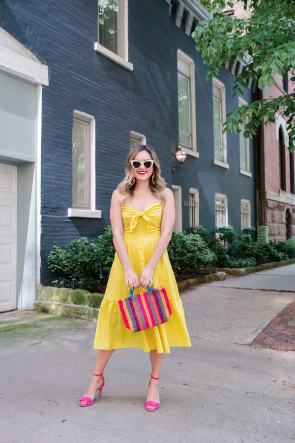 Chicago style blogger Bows & Sequins wearing an Eliza J polka dot tie front dress with a striped mini straw bag.