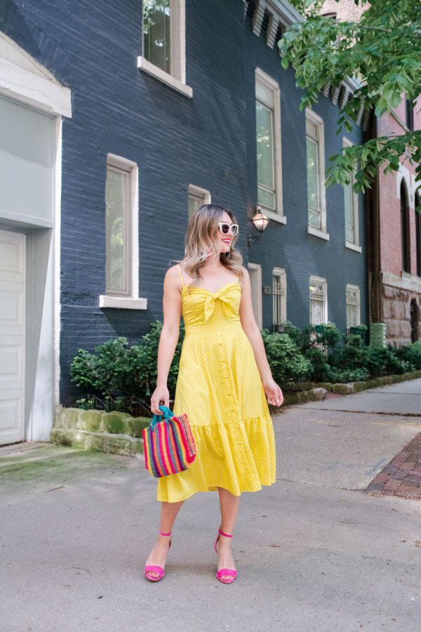 Chicago personal stylist Jessica Sturdy of Bows & Sequins wearing an Eliza J Polka Dot Tie Front Midi Dress with pink heels, a colorful mini bag, and white retro sunglasses.