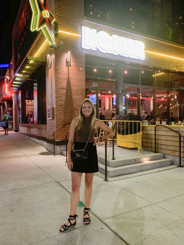 Chicago blogger Jessica Sturdy wearing a mock neck halter bodysuit, suede mini skirt, and M.Gemi ankle wrap sandals, and a Gucci Marmont crossbody bag in front of Big Star in Chicago before a concert.