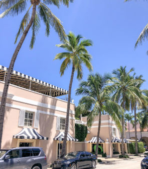 Pink building with black and white striped awnings in Palm Beach Florida with blue skies and palm trees on Worth Avenue.