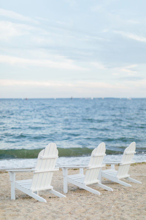 White wooden adirondack chairs on the sand at Wee Burn Beach Club in Connecticut