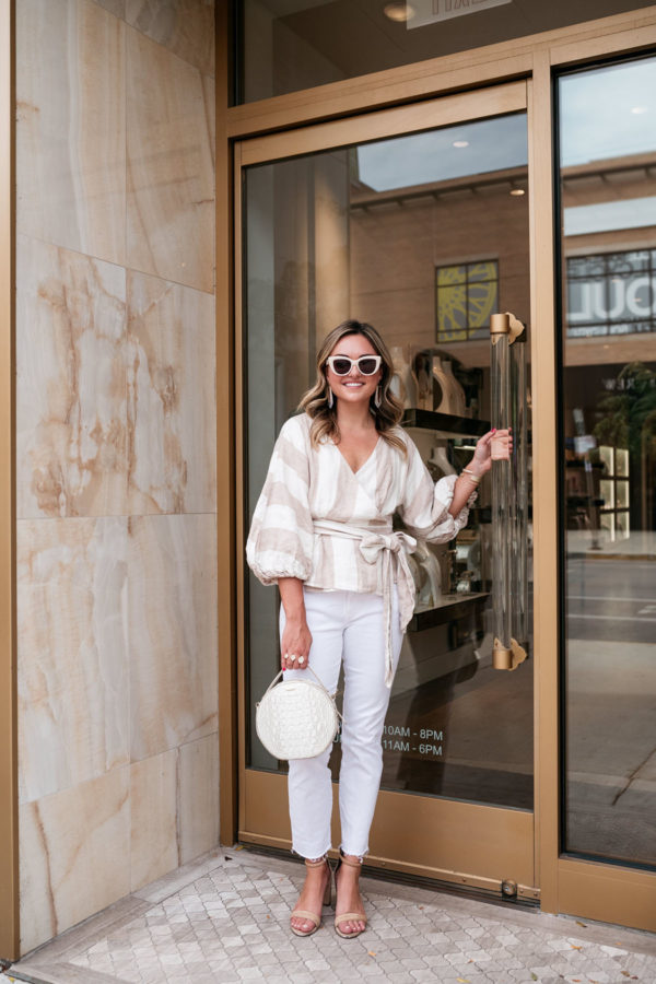 Chicago stylist Jessica Sturdy of Bows & Sequins wearing creamy neutrals for a chic fall outfit. She's wearing a Mara Hoffman linen striped top, white straight leg denim from Vineyard Vines, Kendra Scott jewelry, a Brahmin handbag, and Kenneth Cole nude ankle strap sandals with a block heel.