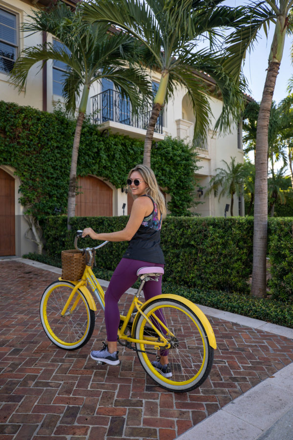 Health and wellness blogger Jessica Sturdy riding a yellow bike from Brazilian Court in Palm Beach, Florida.
