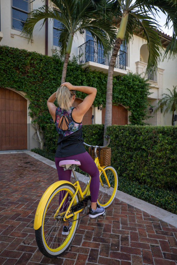 Fitness blogger Jessica Sturdy wearing CALIA by Carrie Underwood Leggings on a yellow bike in Palm Beach, Florida.