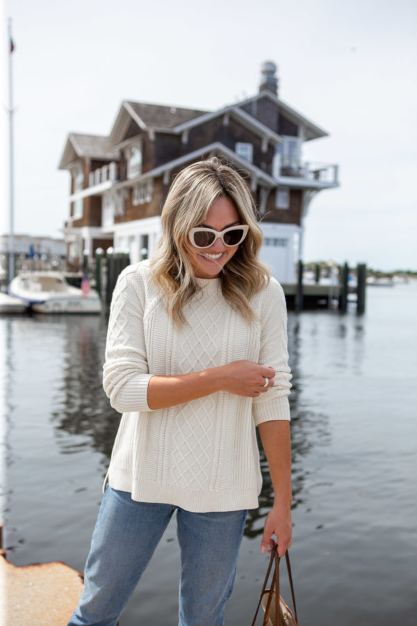 East Coast travel blogger Bows & Sequins wearing a Vineyard Vines fisherman sweater in front of the Watch Hill Yacht Club in Rhode Island