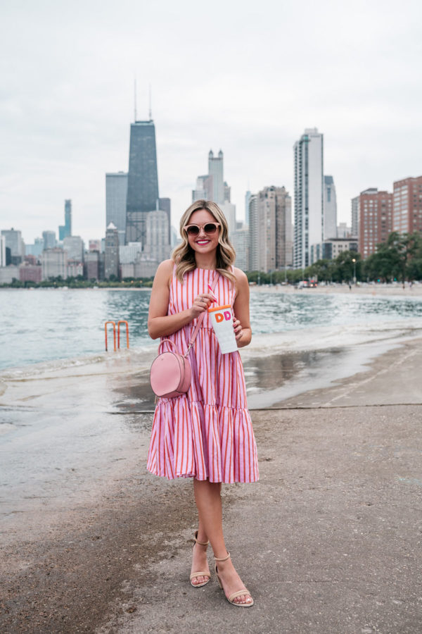 Chicago fashion blogger Jessica Sturdy of Bows & Sequins wearing a MDS Stripes sleeveless peasant dress in pink and orange with a pink Kate Spade crossbody bag, and a Dunkin Donuts reusable tumbler at Oak Street concrete beach with the Chicago skyline in the back.