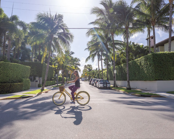 Travel blogger Jessica Sturdy riding a yellow bike in Palm Beach, Florida.