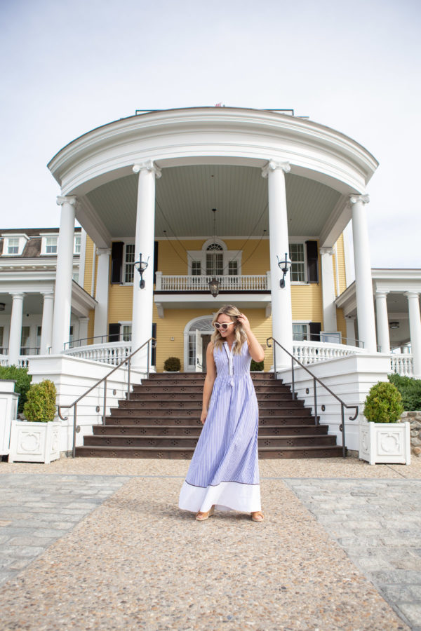 Preppy fashion and lifestyle blogger Jessica Sturdy of Bows & Sequins styling a blue and white striped dress in front of the Ocean House hotel in Rhode Island.