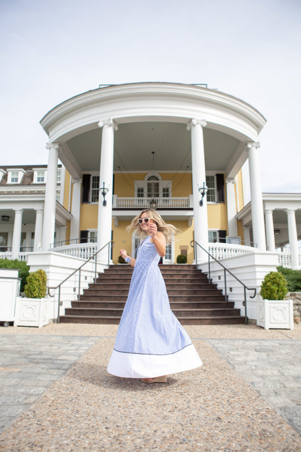 Preppy fashion blogger Bows & Sequins wearing a Vineyard Vines striped maxi dress in front of the steps at Ocean House in Watch Hill, Rhode Island.