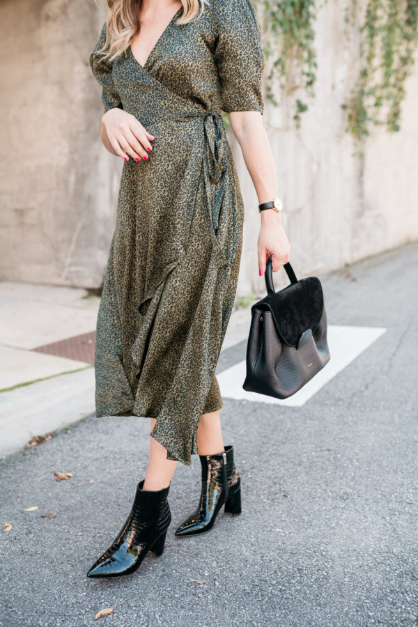 Chicago blogger wearing a green wrap dress with black accessories for fall.