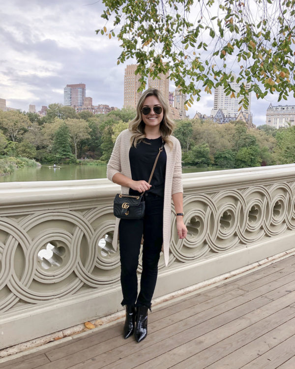 Bows & Sequins in Central Park wearing a Sail to Sable cashmere cardigan with an all black outfit and a Gucci bag.