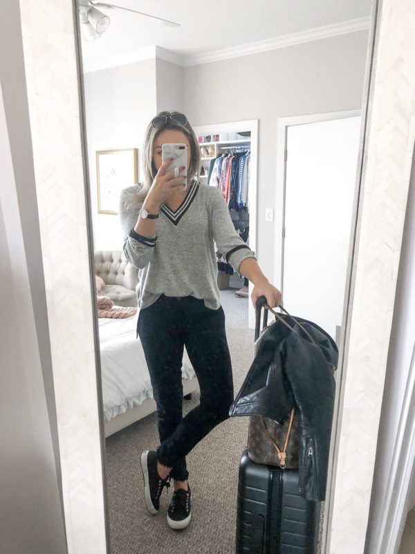 Bows & Sequins styling a Bobeau Varsity V-Neck Sweater with black jeans and Superga sneakers for a casual travel outfit.