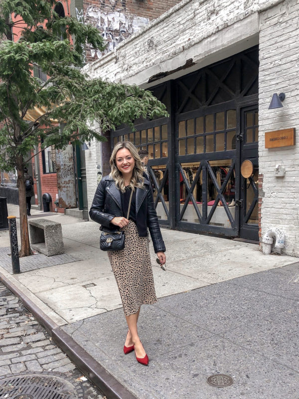 Fashion and beauty blogger Jessica Sturdy of Bows & Sequins wearing a leather moto jacket, Gucci marmont bag, leopard midi skirt, and red slingback pumps on Crosby St in Noho in NYC.