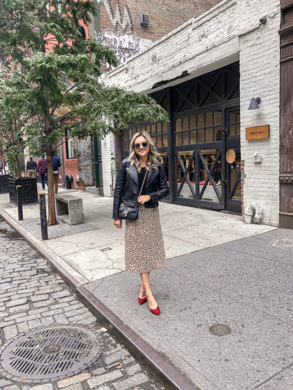 Fashion and lifestyle influencer Jessica Sturdy of Bows & Sequins in NYC in Soho wearing a moto jacket, leopard midi slip skirt, and a red suede Inez slingbacks/