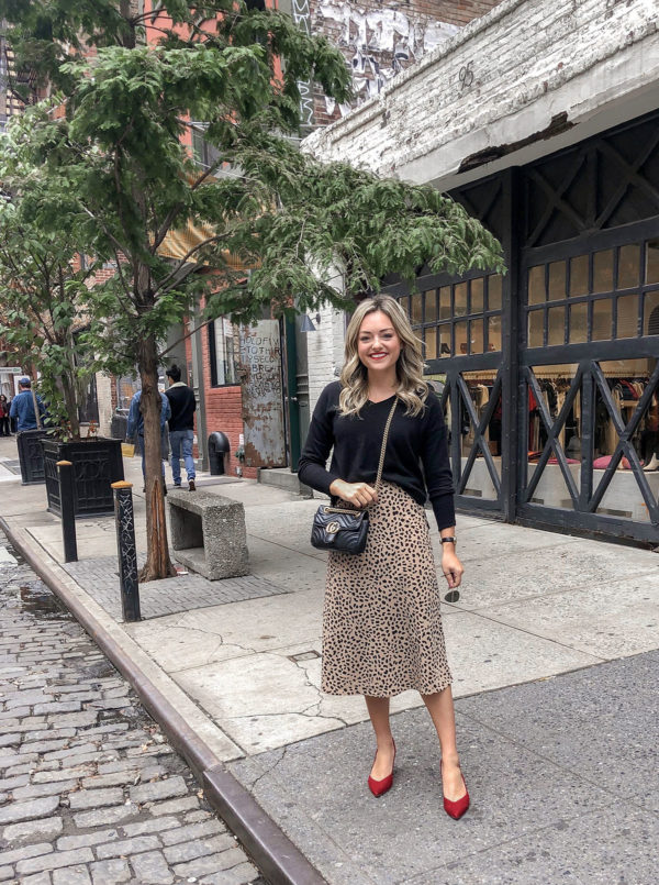 Fashion blogger Jessica Sturdy of Bows & Sequins wearing a black J.Crew sweater, leopard print skirt, red heels, and a Gucci crossbody bag in Soho in NYC.