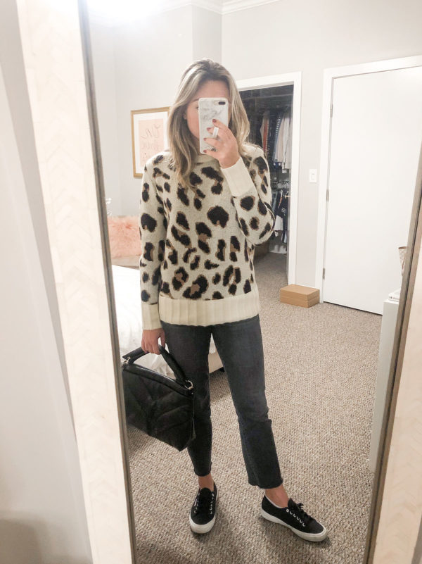 Style blogger Bows & Sequins wearing a Lovers + Friends Leopard Print Sweater from Revolve with grey straight leg jeans and black Superga sneakers.