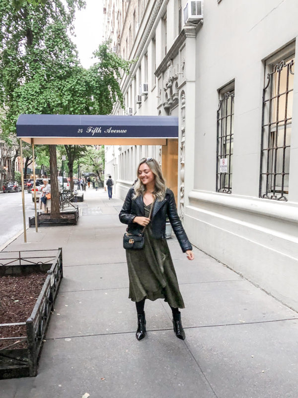 Style blogger Bows & Sequins wearing a black leather moto jacket, Bobeau green leopard dress, Marc Fisher croc booties, and a Gucci bag.