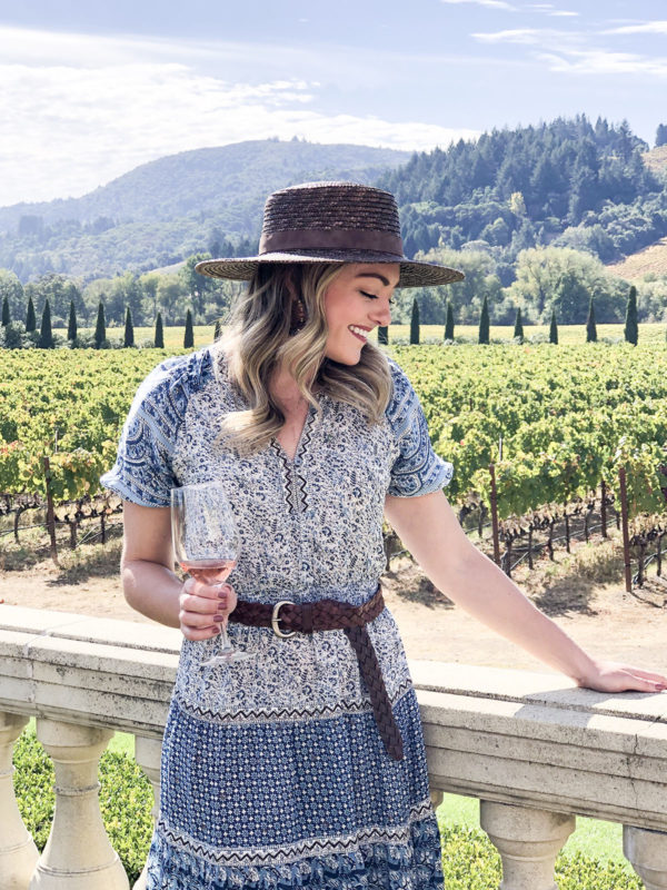 Fashion blogger Jessica Sturdy wearing a brown straw hat and blue printed dress at a wine tasing in Sonoma.