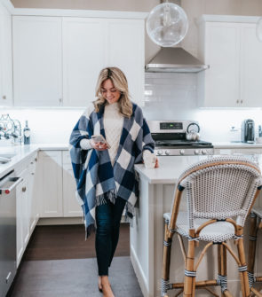 Chicago lifestyle blogger wearing a Vineyard Vines gingham buffalo check cape next to Serena & Lily Riviera Counter Stools in Navy Promo Code.