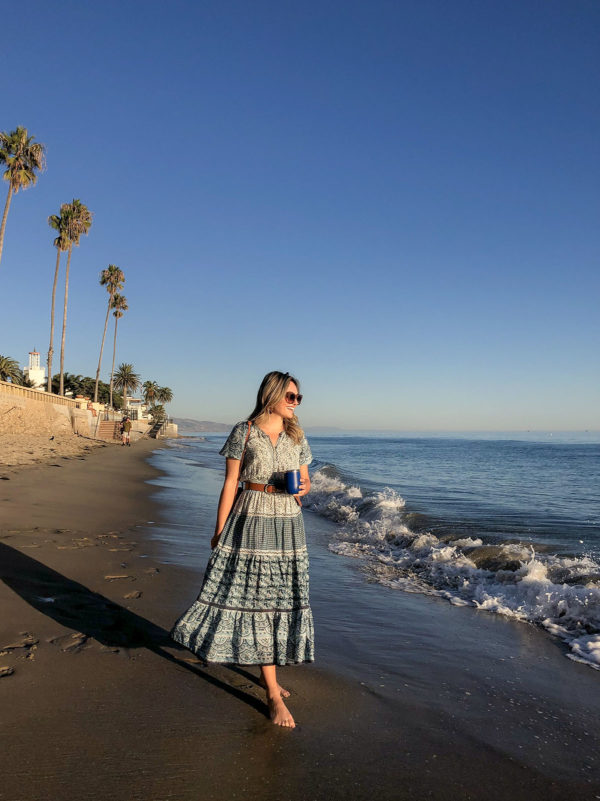 Travel influencer Jessica Sturdy of Bows & Sequins at Butterfly Beach in Santa Barbara, California. She's wearing a Sea New York dress with a Yeti wine glass.