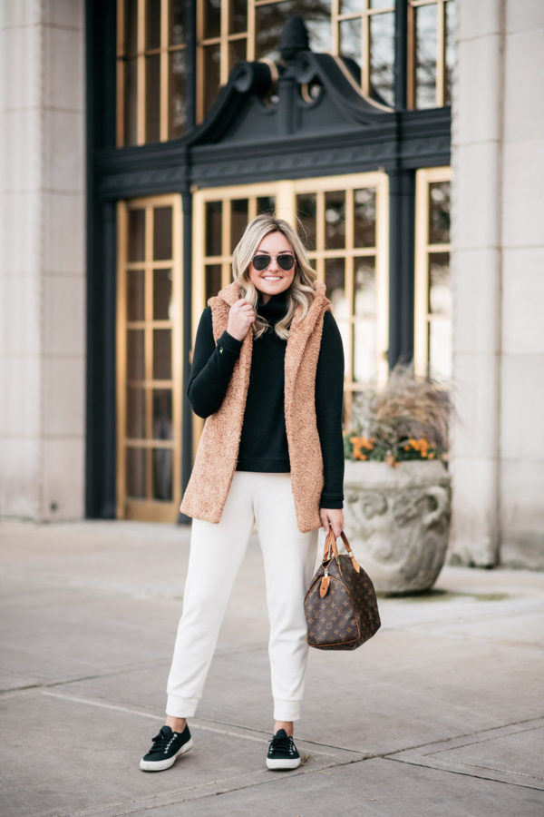 Chicago-based fashion and travel blogger Bows & Sequins styling a camel-colored sherpa vest, white fleece joggers, and a black turtleneck for a cozy weekend outfit that's still put together.