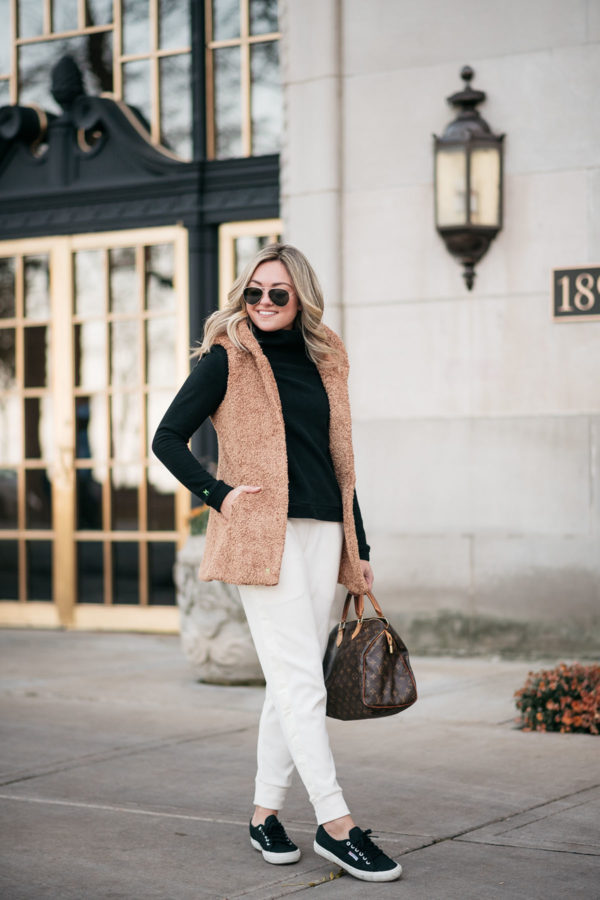 Chicago health & wellness blogger Bows & Sequins wearing a camel fleece vest, black turtleneck, and white jogger sweatpants for a causal weekend outfit.