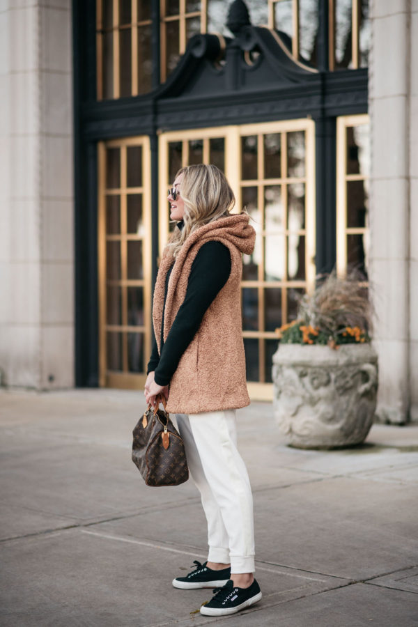 Chicago influencer Bows & Sequins wearing a camel vest, long-sleeve black top, and white jogger pants with Superga Sneakers and Louis Vuitton Speedy.