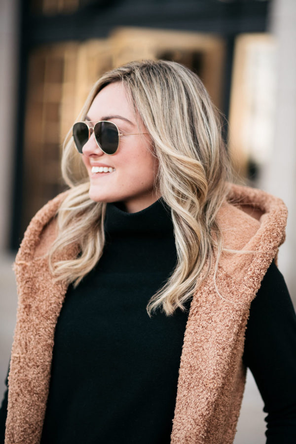 Fashion and beauty blogger Jessica Sturdy wearing a black turtleneck, aviators, and a camel hooded vest. Jessica's cool-toned highlights and loose waves were done at RMCM Salon in Chicago's Gold Coast.