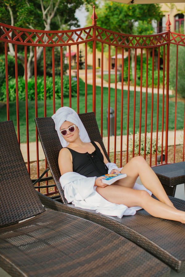 Lifestyle influencer Bows & Sequins by the spa pool at Vintners Inn wearing a black one piece swimsuit and white retro sunglasses.