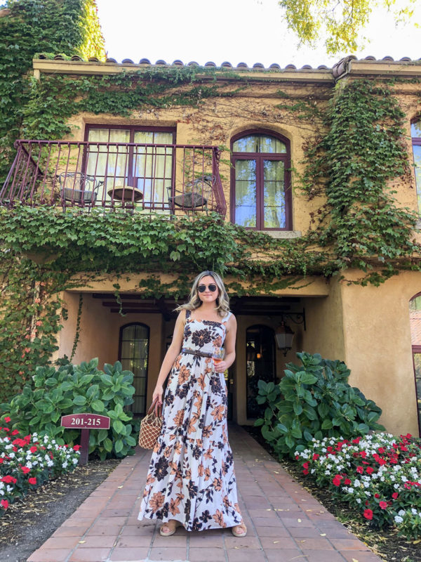 Fashion blogger Bows & Sequins wearing a tiered floral dress by Nicholas at Vintners Inn in Santa Rosa in Sonoma County. She styled it with espadrille wedges and the Staud Mini Moreau Caged Bucket Bag.