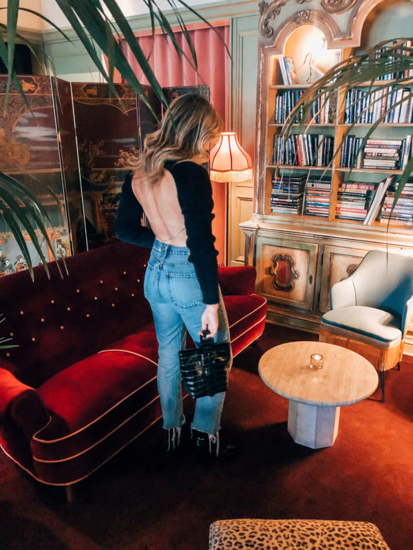 Fashion and lifestyle influencer wearing an open back h:ours sweater with a rhinestone chain from Revolve.