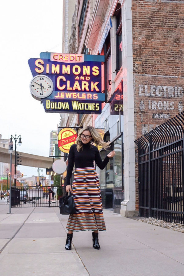 Lifestyle influencer Bows & Sequins styling a striped sweater skirt by Phillip Lim with a ribbed turtleneck bodysuit in Detroit, Michigan.
