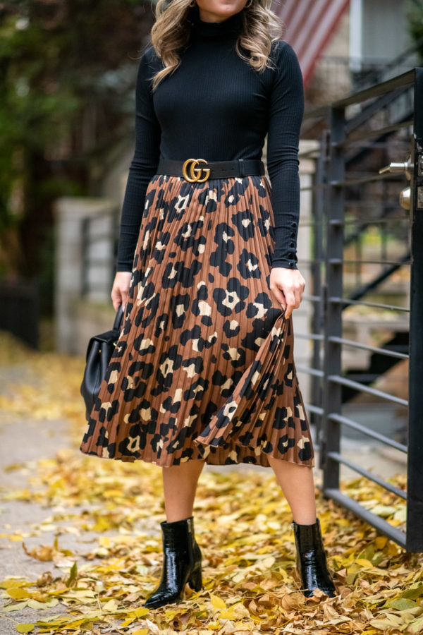 Chicago fashion influencer wearing a pleated skirt with a Gucci belt.